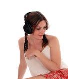 Mujer que se sienta en piso con las auriculares Imágenes de archivo libres de regalías