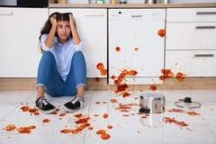 Mujer que se sienta en piso de la cocina con la comida derramada imagenes de archivo