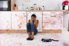 Mujer que se sienta en piso de la cocina con la comida derramada fotografía de archivo