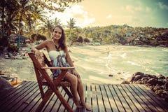 Mujer que se sienta en playa-silla al lado de la playa agradable foto de archivo libre de regalías