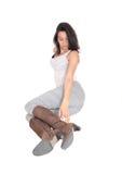 Mujer que se sienta en polainas grises en el piso Imagen de archivo