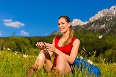 Mujer que se sienta en prado con Mountain View Imágenes de archivo libres de regalías