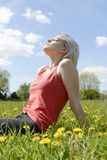 Mujer que se sienta en prado de la flor Fotos de archivo libres de regalías