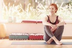 Mujer que se sienta en sala de clase de la yoga foto de archivo libre de regalías