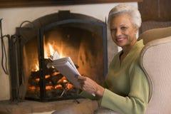 Mujer que se sienta en sala de estar por la chimenea imagenes de archivo