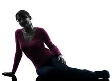 Mujer que se sienta en silhoue integral sonriente del piso imagen de archivo