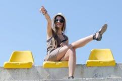 Mujer que se sienta en silla amarilla del estadio Foto de archivo