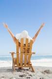 Mujer que se sienta en silla de cubierta en la playa con los brazos para arriba Foto de archivo libre de regalías