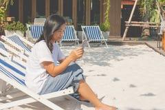 Mujer que se sienta en silla de playa y que juega smartphone en el exterior imagenes de archivo