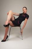 Mujer que se sienta en silla moderna Fotografía de archivo libre de regalías