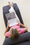 Mujer que se sienta en silla usando la computadora portátil Foto de archivo