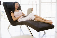 Mujer que se sienta en silla usando la computadora portátil Imagenes de archivo