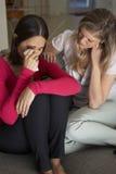 Mujer que se sienta en Sofa Comforting Unhappy Friend Foto de archivo libre de regalías