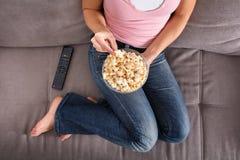 Mujer que se sienta en Sofa Eating Popcorn fotos de archivo libres de regalías