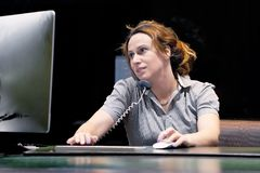 Mujer que se sienta en su escritorio que trabaja y que contesta a una llamada de tel?fono foto de archivo libre de regalías