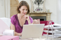 Mujer que se sienta en su escritorio usando la computadora portátil imagen de archivo libre de regalías