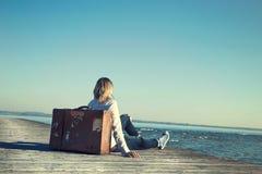Mujer que se sienta en su maleta que espera la puesta del sol en un specta Foto de archivo