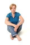 Mujer que se sienta en suelo Fotos de archivo libres de regalías
