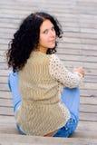 Mujer que se sienta en suelo de madera Imagen de archivo libre de regalías