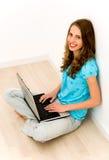 Mujer que se sienta en suelo usando la computadora portátil Foto de archivo libre de regalías