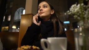 Mujer que se sienta en teléfono que habla del café con el novio tarde para la fecha, relación almacen de metraje de vídeo