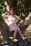 Mujer que se sienta en un árbol en el parque Imágenes de archivo libres de regalías