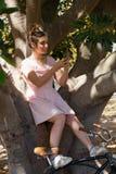 Mujer que se sienta en un árbol y que usa el teléfono móvil Fotografía de archivo