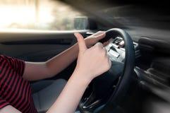 mujer que se sienta en un asiento de carro y que hace un pulgar encima de la muestra Imagen de archivo libre de regalías