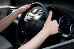 mujer que se sienta en un asiento de carro y que hace un pulgar encima de la muestra Imagen de archivo