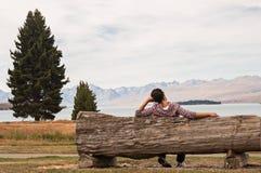 Mujer que se sienta en un banco de madera al lado de un lago Fotografía de archivo libre de regalías