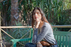 Mujer que se sienta en un banco de parque Foto de archivo libre de regalías