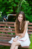 Mujer que se sienta en un banco de parque con su libro Foto de archivo
