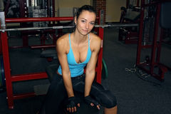 Mujer que se sienta en un banco en el gimnasio listo para hacer una prensa de banco Fotos de archivo