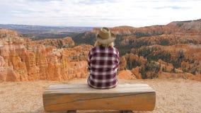 Mujer que se sienta en un banco que mira y que disfruta de la visión y de los paisajes Bryce Canyon foto de archivo libre de regalías