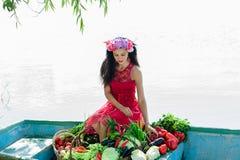 Mujer que se sienta en un barco con las verduras Foto de archivo libre de regalías
