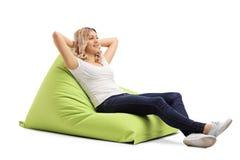Mujer que se sienta en un beanbag cómodo Imágenes de archivo libres de regalías