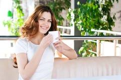 Mujer que se sienta en un café con un coffe Imagenes de archivo