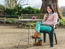 Mujer que se sienta en un café y que mira la cámara con una sonrisa Fotografía de archivo libre de regalías