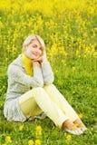 Mujer que se sienta en un campo de flor Imagenes de archivo