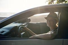 Mujer que se sienta en un coche de alquiler en vacante del día de fiesta fotos de archivo