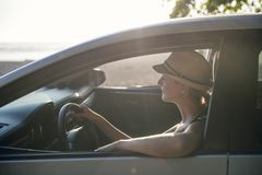 Mujer que se sienta en un coche de alquiler en vacante del día de fiesta fotografía de archivo libre de regalías