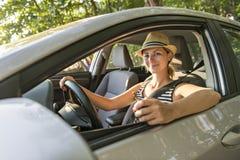 Mujer que se sienta en un coche de alquiler en vacante del día de fiesta foto de archivo libre de regalías