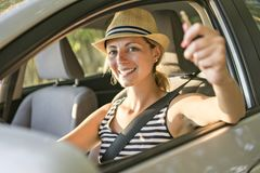 Mujer que se sienta en un coche de alquiler en vacante del día de fiesta imagen de archivo libre de regalías