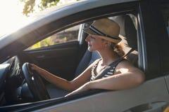 Mujer que se sienta en un coche de alquiler en vacante del día de fiesta fotografía de archivo