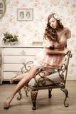 Mujer que se sienta en un cuarto con un interior del vintage Imagenes de archivo