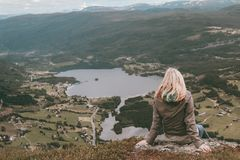 Mujer que se sienta en un pico de montañas mientras que mira en un valle enorme en Noruega imagen de archivo libre de regalías