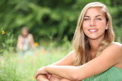 Mujer que se sienta en un prado Foto de archivo libre de regalías