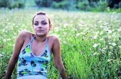 Mujer que se sienta en un prado Imagenes de archivo