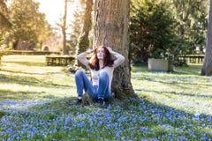 Mujer que se sienta en un prado de la flor de la primavera Fotos de archivo libres de regalías