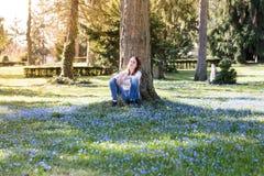 Mujer que se sienta en un prado de la flor de la primavera Fotografía de archivo